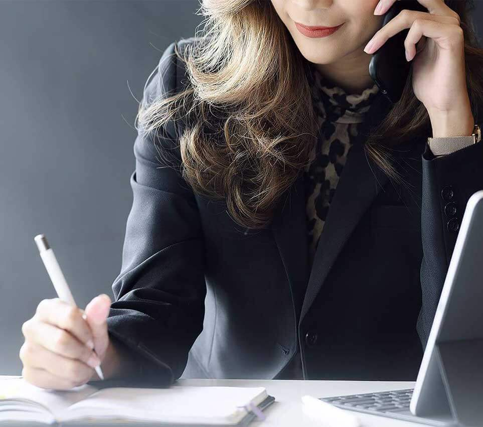 Businesswoman using cellphone while working in modern office.